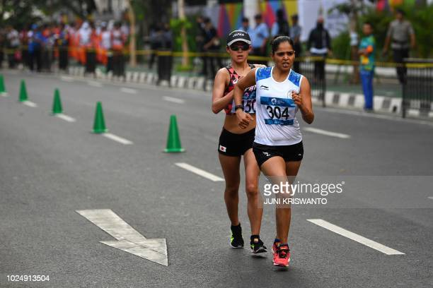 India's Kaur Khusbir and Japan's Kumiko Okada compete in the women's 20km walk race competition during the 2018 Asian Games in Jakarta on August 29...