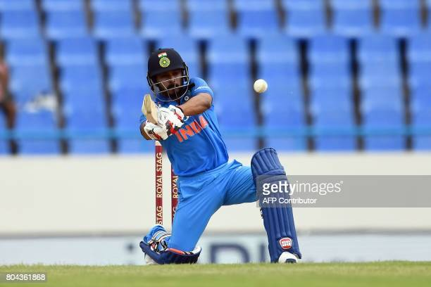 India's Kedar Jadhav hits a boundary during the third One Day International match between West Indies and India at the Sir Vivian Richards Cricket...