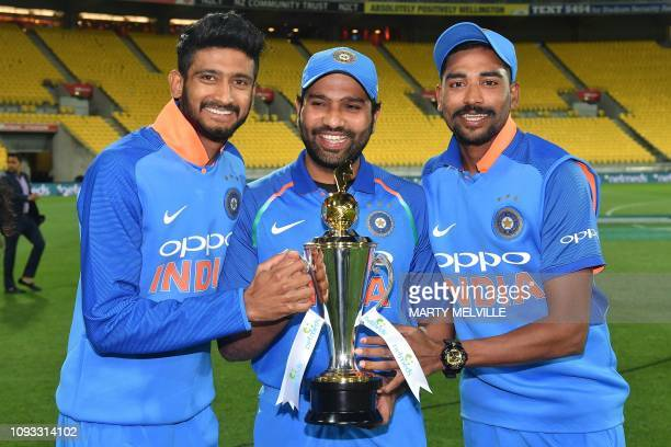 India's Khaleel Ahmed with teammates Rohit Sharma and Mohammed Siraj pose with the trophy after winning the ODI series following the fifth oneday...