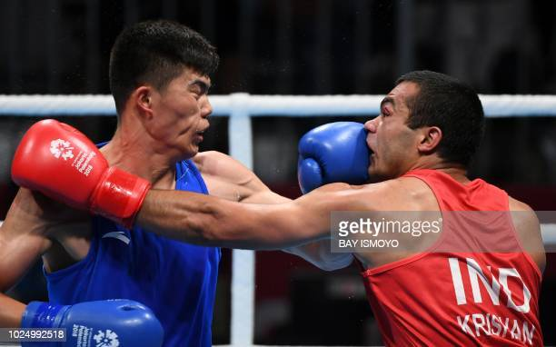 India's Krishan Vikas fights with China's Touheta Erbieke Tanglatihan in their men's middle quarterfinal boxing match at the 2018 Asian Games in...