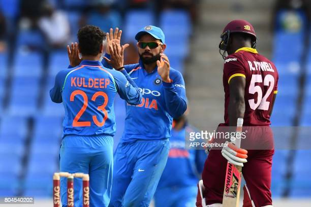 India's Kuldeep Yadav celebrates with team captain Virat Kohli after dismissing West Indies' Rovman Powell during the third One Day International...