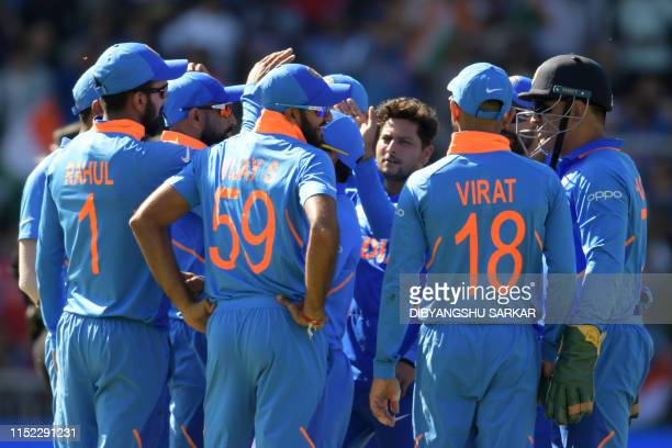 India's Kuldeep Yadav celebrates with teammates after taking the wicket of West Indies' Nicholas Pooran for 28 during the 2019 Cricket World Cup...