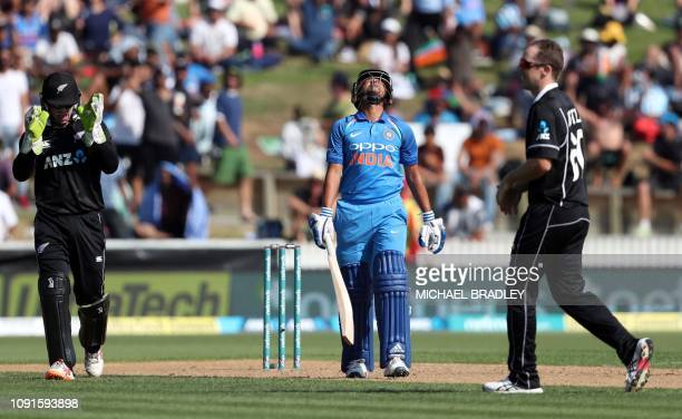 India's Kuldeep Yadav reacts after being dismissed as New Zealand's Tom Latham and Todd Astle look on during the fourth oneday international cricket...