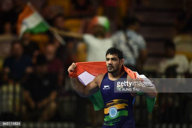 India's Kumar Sushil celebrats with his flag after wrestling against South Africa's Jahannes Botha during the men's freestyle 74 kg gold medal...