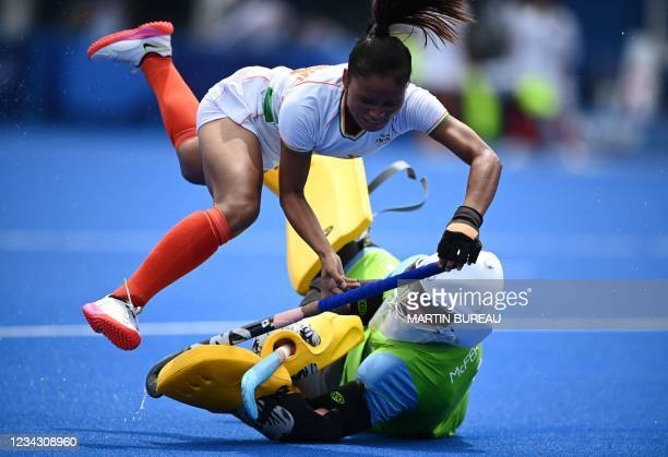 India's Lalremsiami falls over Ireland's goalkeeper Ayeisha McFerran during their women's pool A match of the Tokyo 2020 Olympic Games field hockey...
