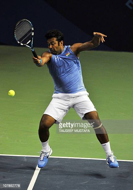 India's Leander Paes teaming with unseen Mahesh Bhupati returns a shot against Australia's Peter Luczak and Paul Hanley during their men's doubles...