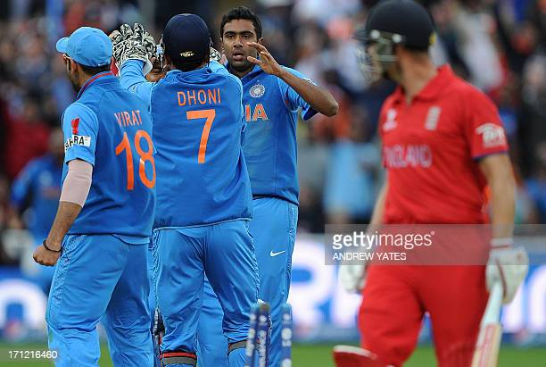 India's Mahendra Sing Dhoni celebrates with bowler India's Ravichandran Ashwin after stumping England's Jonathan Trott during the 2013 ICC Champions...