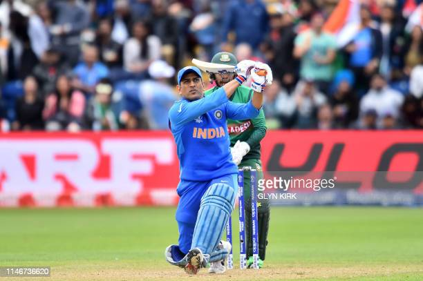 India's Mahendra Singh Dhoni hits a six during the 2019 Cricket World Cup warm up match between Bangladesh v India at Sophia Gardens stadium in...