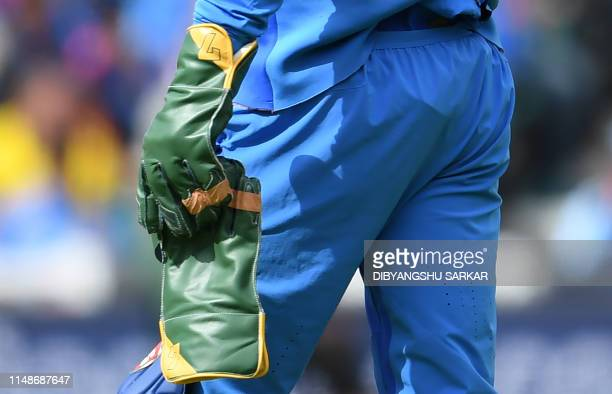 India's Mahendra Singh Dhoni holds his gloves as he prepares to keep wicket during the 2019 Cricket World Cup group stage match between India and...