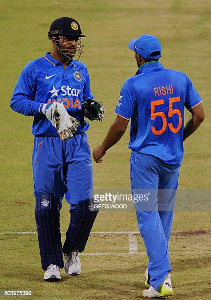 India's Mahendra Singh Dhoni speaks with teammate Rishi Dhawan during the T20 cricket match between India and a Western Australian XI in Perth on...