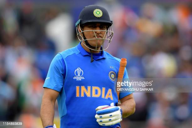 India's Mahendra Singh Dhoni walks off for 50 during the 2019 Cricket World Cup first semifinal between New Zealand and India at Old Trafford in...