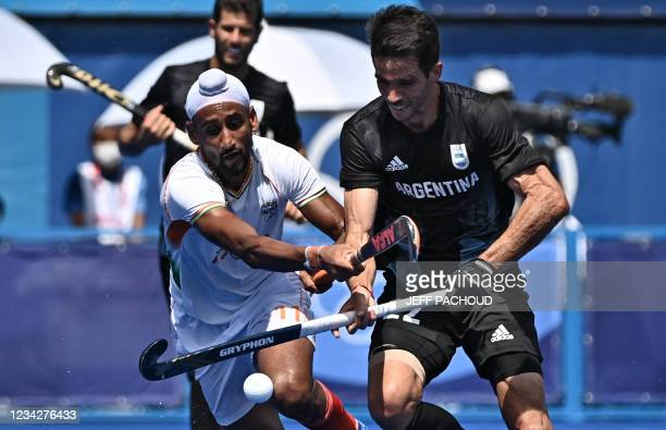 India's Mandeep Singh and Argentina's Matias Alejandro Rey vie for the ball during their men's pool A match of the Tokyo 2020 Olympic Games field...