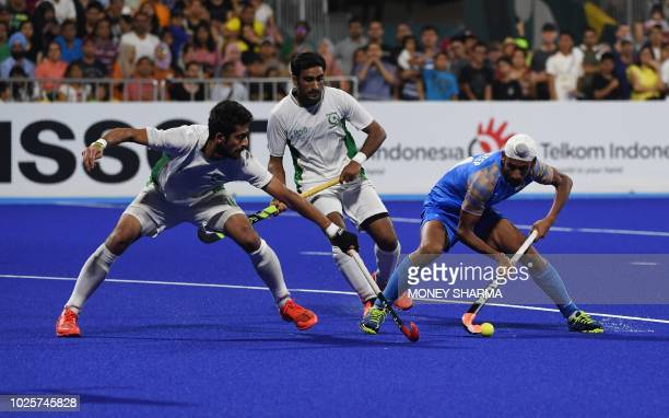 India's Mandeep Singh and Pakistan's Ammad Shakeel Butt competes for the ball during the men's field hockey bronze medal match between India and...