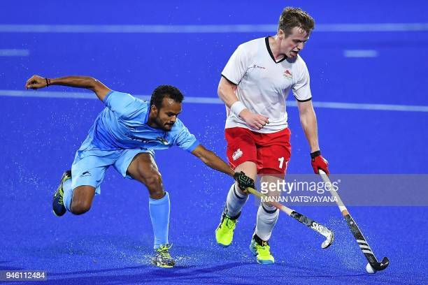India's Mandeep Singh vies for the ball with Ian Sloan of England during their men's field hockey bronze medal match of the 2018 Gold Coast...