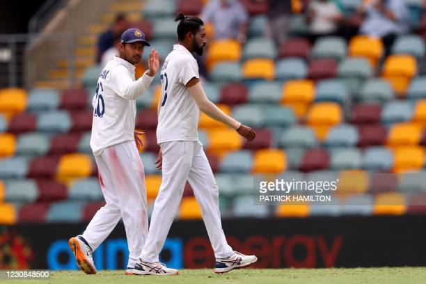 India's Mayank Agarwal and Mohammed Siraj walk towards their fielding positions on day four of the fourth cricket Test match between Australia and...