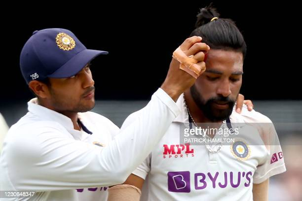 India's Mayank Agarwal rubs the ball on the forehead of his teammate Mohammed Siraj to get sweat to shine it as spiting is prohibited due to the...