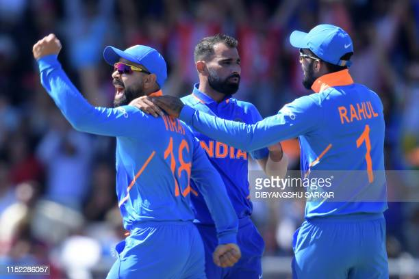 India's Mohammed Shami celebrates with India's captain Virat Kohli after taking the wicket of West Indies' Chris Gayle for 6 during the 2019 Cricket...