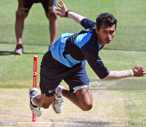 India's Navdeep Saini bowls in the nets during a training session ahead of the second cricket Test match against Australia, in Melbourne on December...