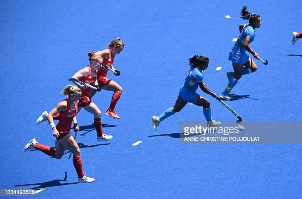 India's Neha Neha carries the ball during the during the women's bronze medal match of the Tokyo 2020 Olympic Games field hockey competition against...