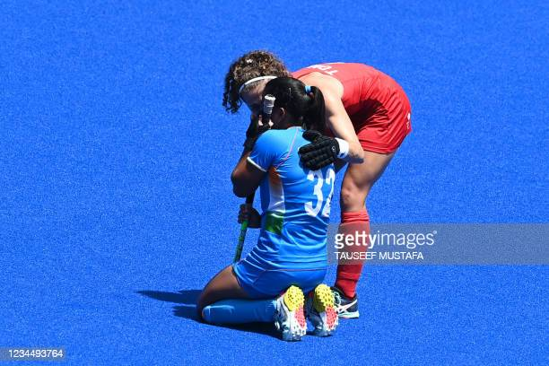 India's Neha Neha is comforted by Britain's Susannah Townsend after losing the women's bronze medal match of the Tokyo 2020 Olympic Games field...