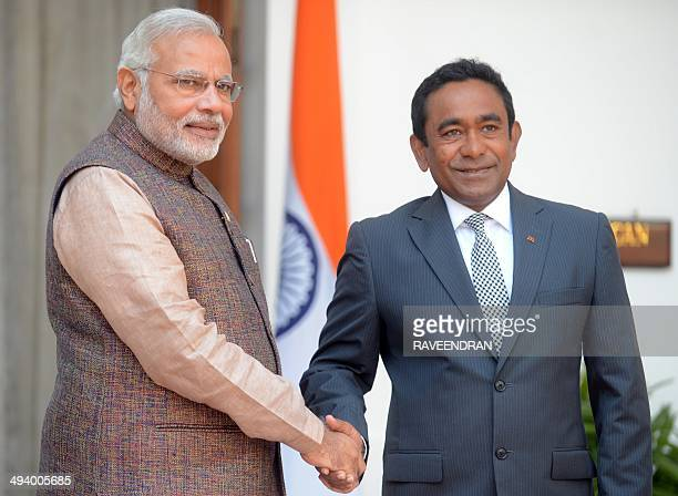 India's newly swornin Prime Minister Narendra Modi shakes hands with Maldives President Abdulla Yameen Abdul Gayoom during a meeting in New Delhi on...