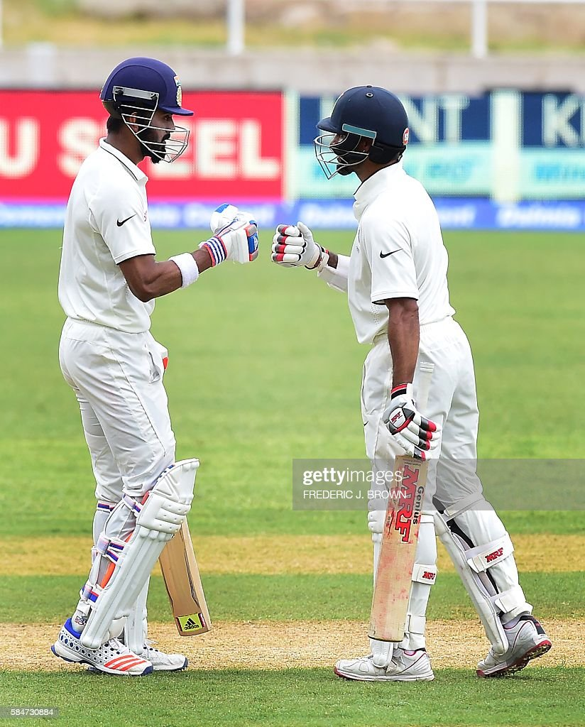 India's opening batsmen Lokesh Rahul (L) and Shikhar Dhawan (R) gesture with each other between innnings against the West Indies on July 30, 2016 in Kingston, Jamaica on the first day of the 2nd Test between India and the West Indies. / AFP / Frederic J. BROWN