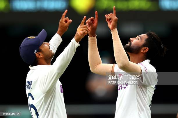 India's paceman Mohammed Siraj celebrates his fifth wicket with teammate Mayank Agarwal on day four of the fourth cricket Test match between...