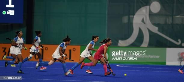 India's players chase Japan's Yukari Mano during the women's field hockey final match between India and Japan at the 2018 Asian Games in Jakarta on...