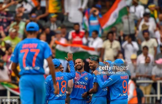 India's players congratulate bowler Hardik Pandya and fielder Shikhar Dhawan after their dismissal of unseen South African batsman David Miller...