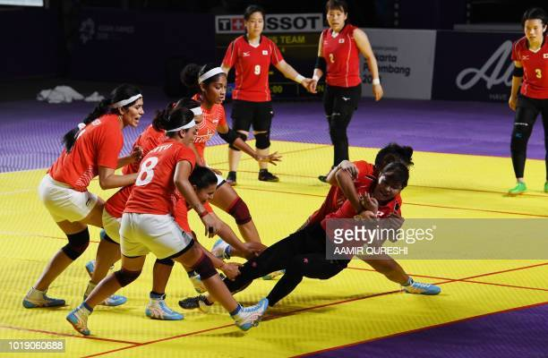 India's players tackle a Japan player during the women's team Group A kabaddi match between India and Japan at the 2018 Asian Games in Jakarta on...