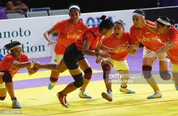 India's players tackle Indonesia's Vinka D Desak Gede Indah during the women's team Group A kabaddi match between India and Indonesia at the 2018...
