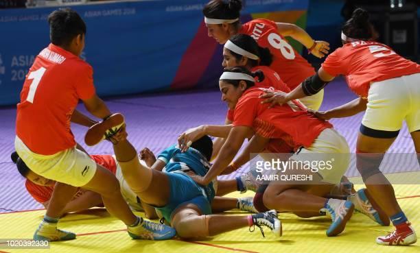India's players tackle Sri Lanka's Nimashi Kokila E Edirisinghage during the women's team Group A kabaddi match between India and Sri Lanka at the...