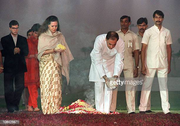 India's Premier Rajiv Gandhi accompanied by his Italianborn wife Sonia son Rahul and daughter Priyanka drops 31 October 1989 flower petals on his...