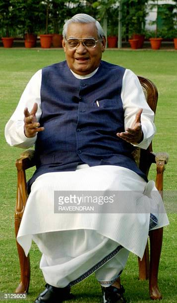 India's Prime Minister Atal Behari Vajpayee gestures as he talks with photographers at his residence in New Delhi 25 March 2004 Vajpayee together...