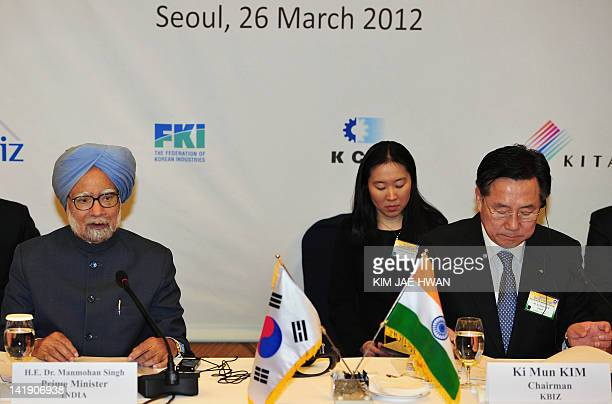 India's Prime Minister Manmohan Singh speaks as Kim Ki-Mun , chairman of the Korea Federation of Small and Medium Businesses , listens during the...