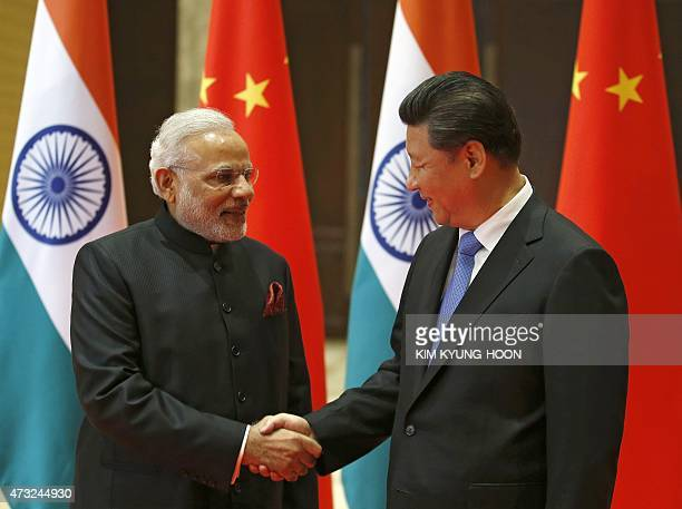 India's Prime Minister Narendra Modi and China's President Xi Jinping shake hands before they hold a meeting in Xian in China's Shaanxi province on...
