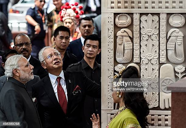 India's Prime Minister Narendra Modi and Malaysia's Prime Minister Najib Razak look at the architecture after inaugurating the 'Torana Gate'...