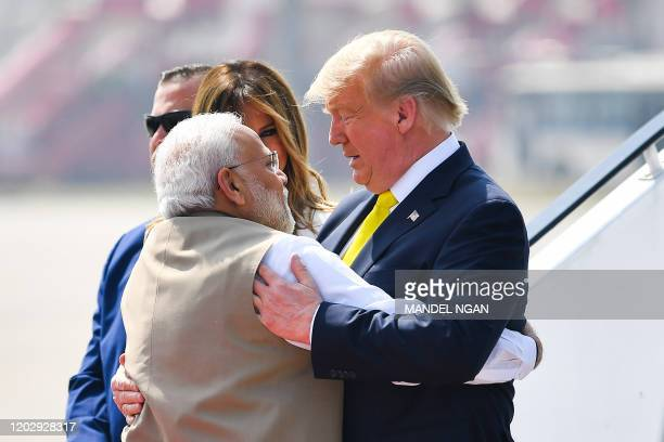India's Prime Minister Narendra Modi embraces US President Donald Trump upon his arrival at Sardar Vallabhbhai Patel International Airport in...