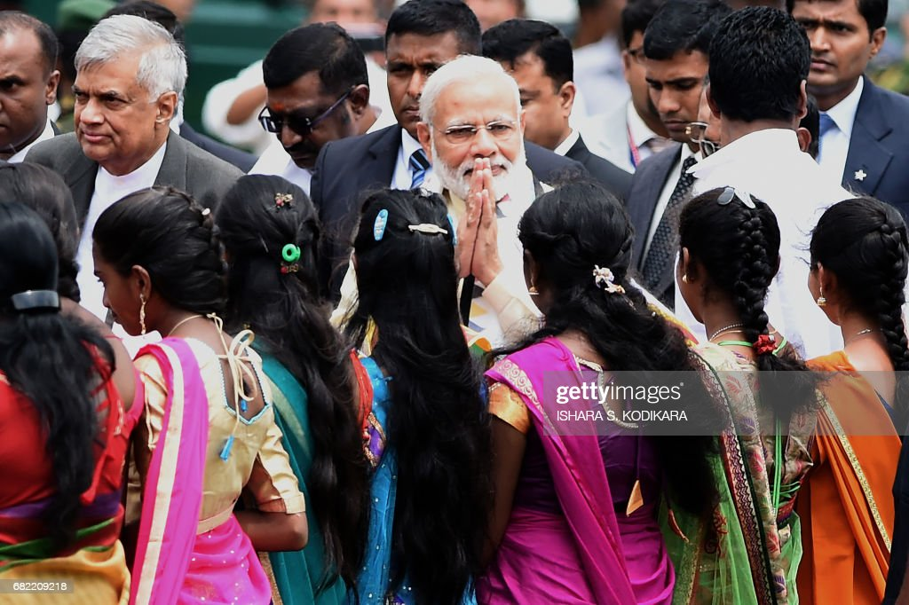 India's Prime Minister Narendra Modi (C) gestures to bystanders as he arrives with arrives with Sri Lankan Prime Minister Ranil Wickremesinghe (L) to address a public rally in the tea-growing town of Norwood, some 80kms east of Colombo on May 12, 2017. Indian Prime Minister Narendra Modi declared that his desire for a 'quantum jump' in relations with Sri Lanka, as New Delhi jostles with regional rival Beijing for influence in the island nation. / AFP PHOTO / Ishara S. KODIKARA
