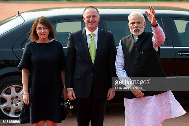 India's Prime Minister Narendra Modi gestures while posing with New Zealand Prime Minister John Key and his wife Bronagh Key during a ceremonial...
