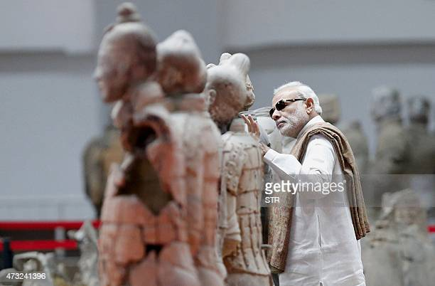 India's Prime Minister Narendra Modi inspects a sculpture of the Terracotta Army a World Heritage Site in the city of Xian in northwest China's...