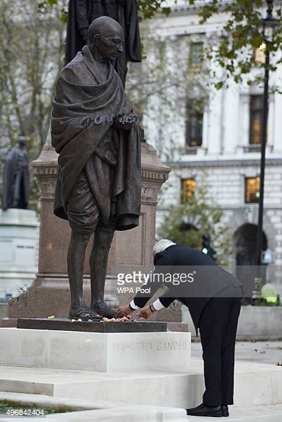 India's Prime Minister Narendra Modi places flower petals on the statue of Mahatma Ghandi in Parliament Square during an official three day visit on...