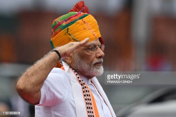India's Prime Minister Narendra Modi salutes as he reviews a guard of honour during a ceremony to celebrate country's 73rd Independence Day, which...