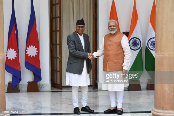 India's Prime Minister Narendra Modi shakes hands with his Nepali counterpart Sher Bahadur Deuba prior to a meeting and agreement signing ceremony in...