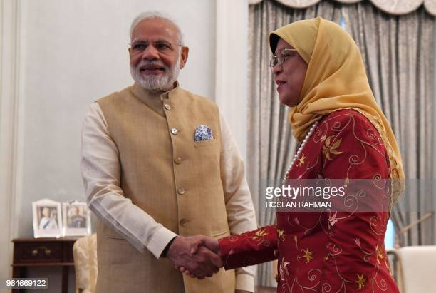 Indias Prime Minister Narendra Modi shakes hands with Singapore's President Halimah Yacob at the Istana presidential palace in Singapore on June 1...