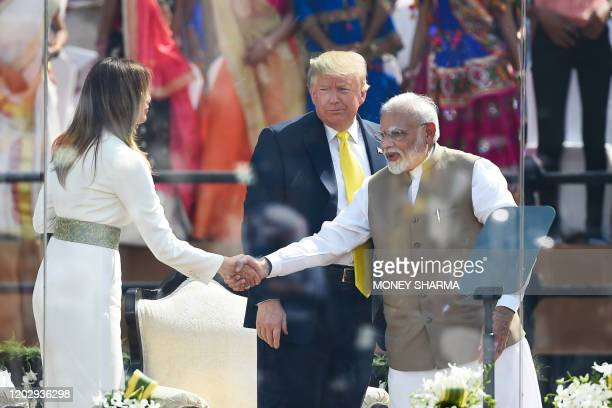 India's Prime Minister Narendra Modi shakes hands with US First Lady Melania Trump as President Donald Trump looks on during 'Namaste Trump' rally at...