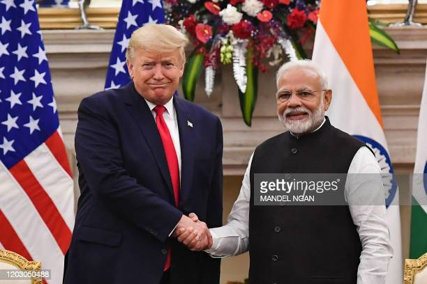 India's Prime Minister Narendra Modi shakes hands with US President Donald Trump before a meeting at Hyderabad House in New Delhi on February 25,...
