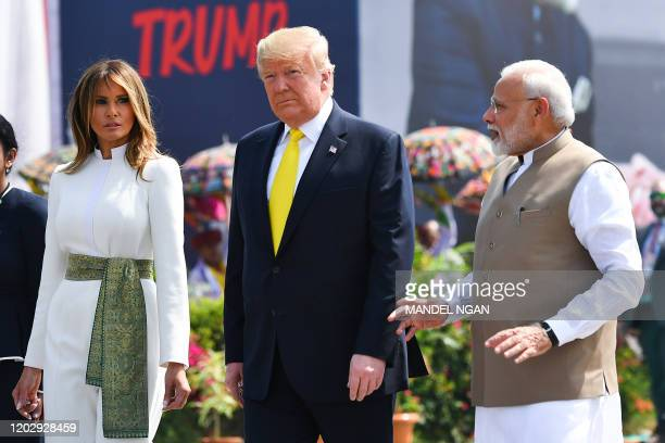India's Prime Minister Narendra Modi speaks with US President Donald Trump and First Lady Melania Trump upon their arrival at Sardar Vallabhbhai...