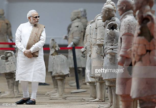 India's Prime Minister Narendra Modi takes looks at sculptures of the Terracotta Army a World Heritage Site in the city of Xian in northwest China's...