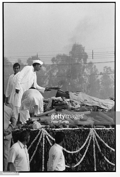 India's Prime Minister Rajiv Gandhi adds fuel to his mother's funeral pyre following her assassination in 1984 Cremation is the traditional funeral...